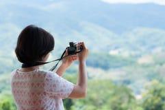 Mulher asiática nova que guarda a câmera Foto de Stock