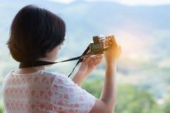 Mulher asiática nova que guarda a câmera Fotografia de Stock