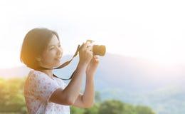 Mulher asiática nova que guarda a câmera Imagem de Stock