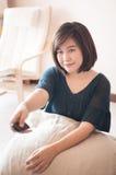 Mulher asiática nova que guarda o controlo a distância imagem de stock