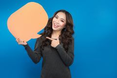 Mulher asiática nova que guarda uma bolha do discurso em um fundo azul Imagem de Stock
