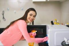 Mulher asiática nova que limpa a cozinha com o pulverizador detergente fotografia de stock royalty free