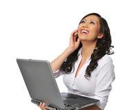 Mulher asiática nova que ri e que prende um portátil foto de stock