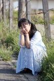 Mulher asiática nova que senta-se em uma cerca do barbwire imagem de stock royalty free