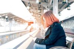 Mulher asiática nova que senta-se no trem de espera do banco e que usa m fotos de stock