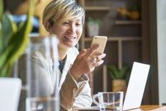 Mulher asiática nova que sorri usando o telefone e o portátil espertos na cafetaria foto de stock