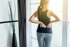 Mulher asiática nova que tem a dor da cintura ou do flanco, sentimento fêmea esgotado e doloroso foto de stock royalty free