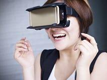 Mulher asiática nova que tenta vidros de VR Fotografia de Stock