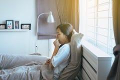 A mulher asiática nova que tosse e que senta-se em sua cama após acorda fotos de stock