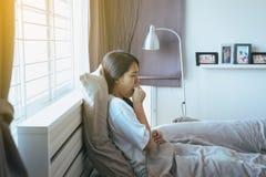 Mulher asiática nova que tosse e que senta-se em sua cama, conceito da saúde imagem de stock royalty free