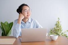Mulher asiática nova que trabalha no portátil na mesa de escritório domiciliário E sente-se no queixo de descanso da tabela dispo imagens de stock