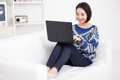 Mulher asiática nova que usa o portátil Fotografia de Stock