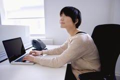 Mulher asiática nova que usa o portátil ao olhar afastado imagens de stock