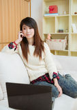 Mulher asiática nova que usa um portátil e um telemóvel Imagem de Stock