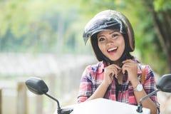 Mulher asiática nova que veste um capacete antes de montar uma motocicleta sobre foto de stock