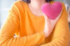 Mulher asiática nova romântica com o descanso coração-dado forma cor-de-rosa foto de stock