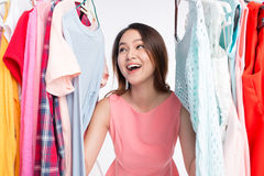 Mulher asiática nova surpreendida na loja, espreitando para fora através do clothin Imagem de Stock