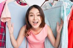 Mulher asiática nova surpreendida na loja, espreitando para fora através do clothin Imagem de Stock Royalty Free
