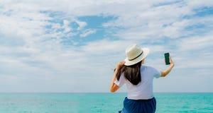 A mulher asiática nova veste o smartphone do uso do chapéu de palha que toma o selfie no cais de madeira Férias de verão na praia foto de stock royalty free