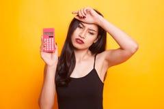 A mulher asiática obteve a dor de cabeça com calculadora Foto de Stock