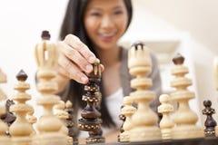 Mulher asiática oriental chinesa que joga a xadrez Fotografia de Stock