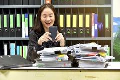 Mulher asiática preguiçosa do escritório que usa o telefone esperto móvel no tempo de funcionamento fotos de stock
