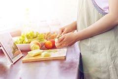 A mulher asiática prepara ingredientes cozinhando segue o cozimento em linha imagens de stock
