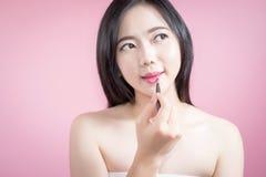 Mulher asiática que aplica o batom cor-de-rosa em seus bordos, cara da beleza e composição natural, fundo branco isolado Fotografia de Stock Royalty Free
