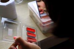 Mulher asiática que aplica o cosmético da composição seus mounth e cara foto de stock royalty free