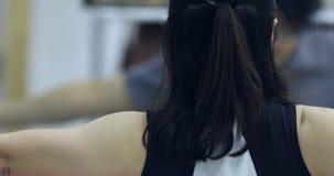 Mulher asiática que aprende a ioga em casa