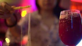 Mulher asiática que bebe o cocktail vermelho no bar dinning claro de néon filme