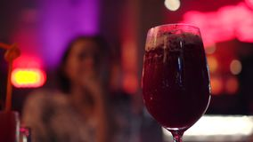 Mulher asiática que bebe o cocktail vermelho no bar dinning claro de néon video estoque