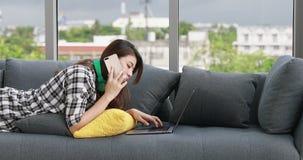 Mulher asiática que coloca no sofá vídeos de arquivo