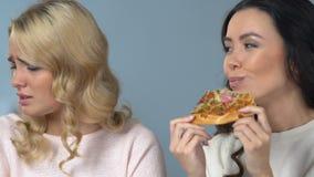 Mulher asiática que come avidamente a pizza na frente de seu amigo que que mantém a dieta filme