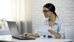 Mulher asiática que datilografa no portátil em casa que verifica a correspondência, letras de resposta foto de stock