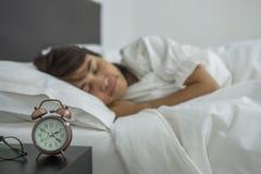 Mulher asiática que dorme na cama, encontro fêmea novo no interior do quarto na noite imagem de stock