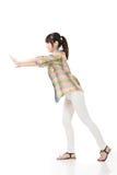 Mulher asiática que empurra ou que inclina-se na parede Foto de Stock