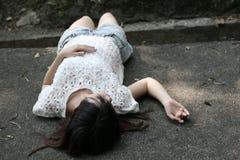 Mulher asiática que encontra-se no assoalho áspero do cimento fotografia de stock royalty free
