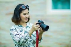Mulher asiática que guarda e que verifica a foto da câmera Imagens de Stock