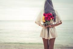 Mulher asiática que guarda flores dentro atrás e que espera alguém miliampère Fotografia de Stock Royalty Free