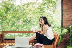 Mulher asiática que guarda o copo de café ao sentar-se perto da janela no crea Imagens de Stock