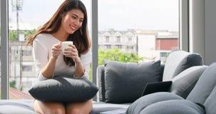 Mulher asiática que guarda o copo de café e que usa o portátil vídeos de arquivo