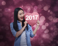Mulher asiática que guarda o coração vermelho com número 2017 Fotografia de Stock Royalty Free