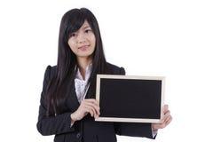 Mulher asiática que guarda o quadro-negro pequeno fotos de stock