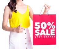 Mulher asiática que guarda o saco de compras com a VENDA de 50% escrita isolada Imagem de Stock