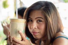 Mulher asiática que guarda o vidro do café congelado fotografia de stock royalty free