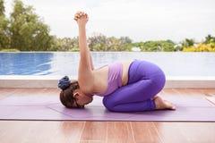 Mulher asiática que joga a ioga para a saúde ao lado da associação de água foto de stock