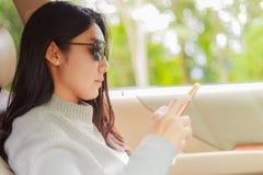 Mulher asiática que joga o smartphone no carro preto fotografia de stock royalty free
