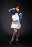 Mulher asiática que levanta com o cartaz vazio no estúdio foto de stock