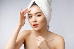 Mulher asiática que olha a espinha na cara A jovem mulher tenta remover sua espinha Conceito do cuidado de pele da mulher Isolado fotografia de stock royalty free